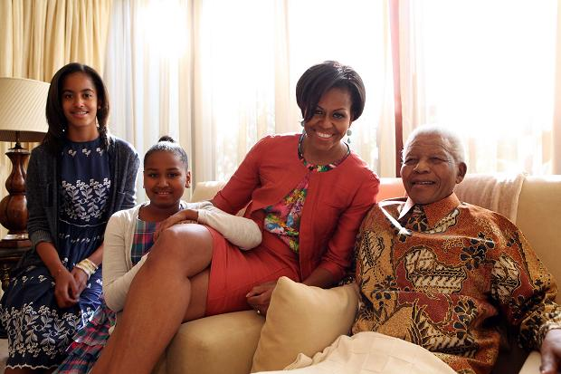 Former South African President Nelson Mandela, right, poses with US First Lady Michelle Obama, second right, and her daughters Malia, left, and Sasha, at his home in Johannesburg
