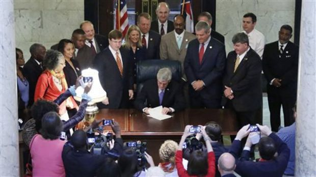 Surrounded by elected officials, Republican Gov. Phil Bryant, seated at center, signs the Teacher Pay Raise bill in the rotunda of the Capitol in Jackson, Miss. on Monday, April 22, 2014. The legislation gives public school teachers two across-the-board pay raises worth $2,500 over the next two years, and would eligible for merit payments in 2016-2017. (AP Photo/Rogelio V. Solis)