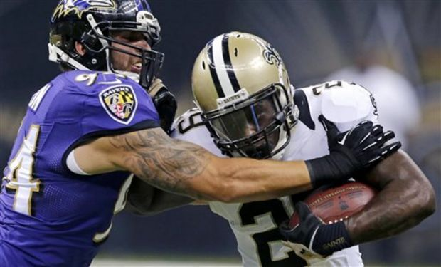 New Orleans Saints running back Khiry Robinson (29) carries against Baltimore Ravens linebacker John Simon (94) during the first half of an NFL preseason football game in New Orleans, Thursday, Aug. 28, 2014. (AP Photo/Bill Haber)
