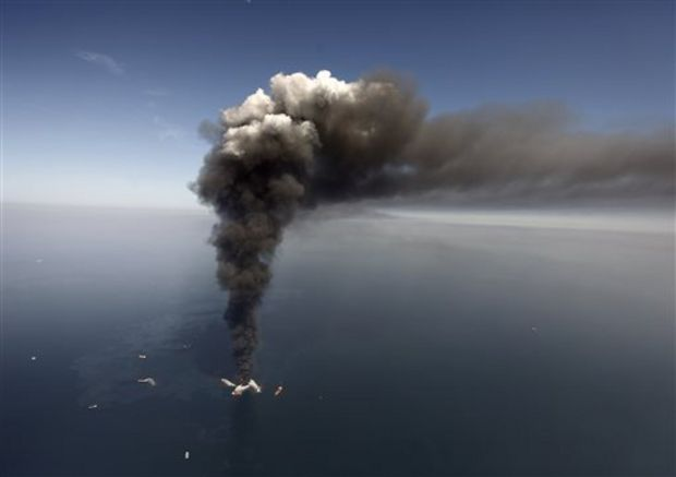 In this April 21, 2010 file photo, oil can be seen in the Gulf of Mexico, more than 50 miles southeast of Venice on Louisiana's tip, as a large plume of smoke rises from fires on BP's Deepwater Horizon offshore oil rig. (Gerald Herbert/The Associated Press)