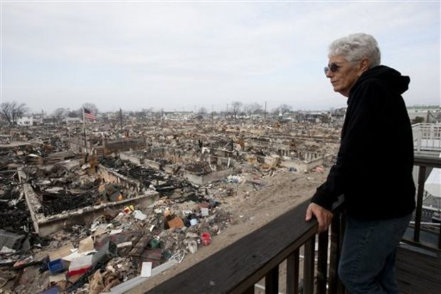 In this Dec. 4, 2012 photo, Anne Hoerning looks from her second floor balcony at the remains of the over 100 houses that burned during Superstorm Sandy in the Breezy Point section of the Queens borough of New York. (Mark Lennihan/The Associated Press)