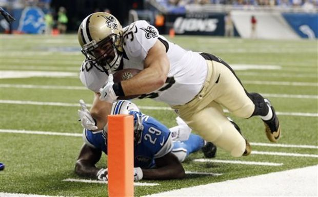 New Orleans Saints fullback Austin Johnson, defended by Detroit Lions cornerback Cassius Vaughn (29), scores on a 13-yard touchdown run during the first half of an NFL football game in Detroit, Sunday, Oct. 19, 2014. (AP Photo/Paul Sancya)