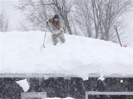 Tom Mudd clears snow from the roof of his house on Thursday, Nov. 20, 2014, in Cheektowaga, N.Y. A new blast of lake-effect snow pounded Buffalo for a third day piling more misery on a city already buried by an epic, deadly snowfall that could leave some areas with nearly 8 feet of snow on the ground when it's all done. (AP Photo/Mike Groll)