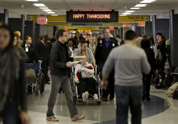 "In this Nov. 26, 2013 file photo, travelers walk under a sign reading ""Happy Thanksgiving"" at LaGuardia Airport in New York. There will be 12.3 million roundtrip passengers, globally, on U.S. airlines during the 2014 holiday travel period, up 1.5 percent from 2013, according to the industry's lobbying group, Airlines for America. (AP Photo/Seth Wenig, File)"