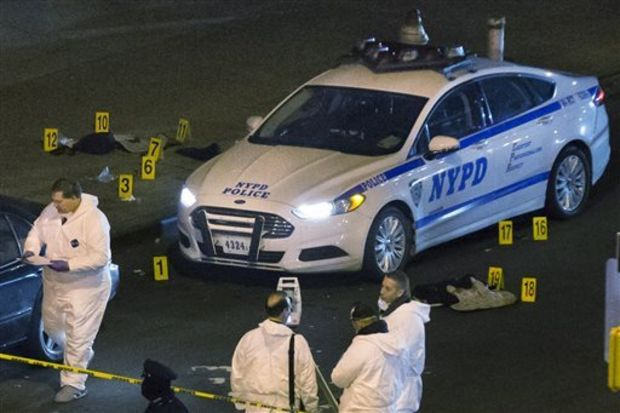 Bulletproof vests lie on each side of an NYPD patrol car as investigators work at the scene where two NYPD officers were shot in the Bedford-Stuyvesant neighborhood of the Brooklyn borough of New York on Saturday, Dec. 20, 2014. Police said an armed man walked up to the officers sitting inside the patrol car and opened fire before running into a nearby subway station and committing suicide. Both police officers were killed. (AP Photo/John Minchillo)