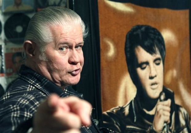 """In this Dec. 9, 2009 file photo, Paul MacLeod stands before a poster of Elvis Presley in the antebellum home and a private Elvis Presley museum he calls """"Graceland Too,"""" in Holly Springs, Miss. MacLeod, a lifetime Elvis fanatic, was found dead on the porch of his home early Thursday, July 17, 2014, two days after authorities say he shot and killed a man who forced his way into the attraction. (AP Photo/Rogelio V. Solis, File)"""