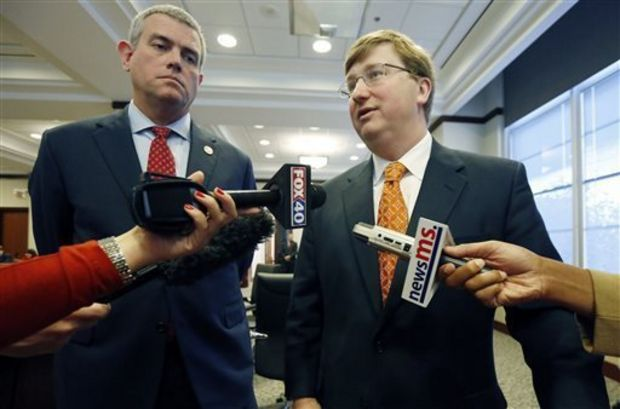 Mississippi Lt. Gov. Tate Reeves, right speaks to reporters on the merits of the Joint Legislative Budget Committee's $6 billion spending blueprint for fiscal 2016, which begins July 1, following its release, Tuesday, Dec. 9, 2014, in Jackson, Miss., while House Speaker Philip Gunn, R-Clinton, listens. The committee is proposing a slightly smaller Mississippi budget for the coming year, despite their expectation that state revenue will increase. (AP Photo/Rogelio V. Solis)