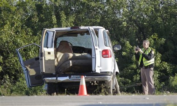 A Florida Highway investigators takes a picture of a van that crashed into canal at the intersection of US 27 and State Road 78 West, Monday, March 30, 2015, near Moore Haven, Fla. Eight people were killed and 10 injured when the church van ran through a stop sign, crossed all four lanes of a rural highway and crashed into in a canal. (AP Photo/Luis M. Alvarez)
