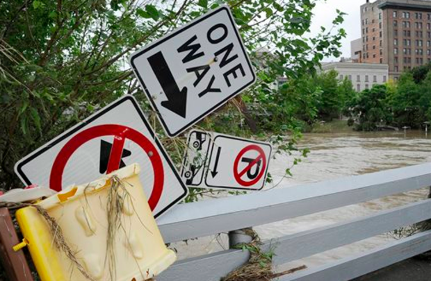 A grouping of road signs perch on a bridge railing over the overrun banks of the bayou in downtown Houston, Tuesday, May 26, 2015. Floodwaters kept rising Tuesday across much of Texas as storms dumped almost another foot of rain on the Houston area, stranding hundreds of motorists and inundating the famously congested highways that serve the nation's fourth-largest city. (AP)