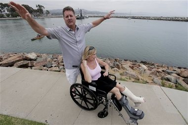 Dirk Frickman, left, describes how a dolphin leaped onto his boat on June 21, 2015, in Southern California breaking both of his wife Chrissie's ankles while boating near Dana Point, Calif., Wednesday, July 1, 2015. Dirk, pulled her out and called authorities as he headed toward an Orange County harbor. While he steered, he splashed water on the about 350-pound dolphin to keep it alive as it thrashed around and bled from some cuts. (AP Photo/Chris Carlson)