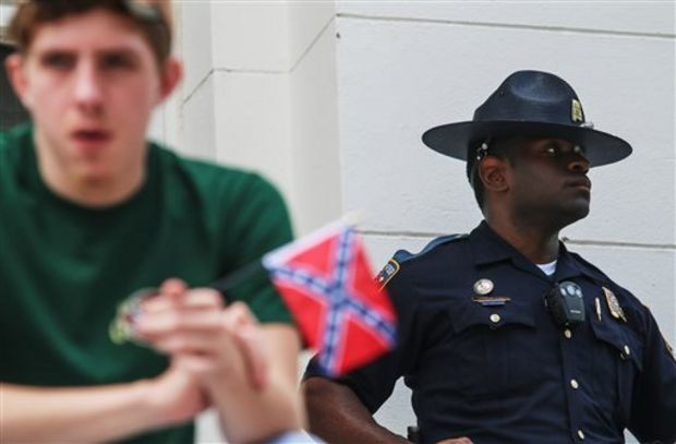 An Alabama state trooper stands guard as a pro-Confederate rally is held at the Alabama state capitol building in Montgomery, Ala. on Saturday, June 27, 2015. The rally was held by locals and members of several Southern heritage organizations who oppose the recent removal of Confederate flags from a monument at the capitol honoring Confederate Civil War soldiers. (AP Photo/Ron Harris
