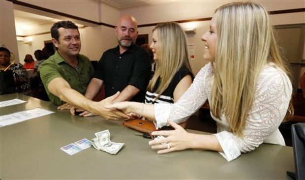 Couples Duane Smith, 40, left, and Knol Aust, 39, of Jackson, Miss., greet couple Laurin Locke, 24, second from right and her partner Tiffany Brosh, 26, of Pearl, Miss., as they wait to apply for marriage licenses at the Hinds County Courthouse in Jackson, Miss., Friday, June 26, 2015, moments of the U.S. Supreme Court ruling that legalizes gay marriage nationwide. The couples were the first two to apply. However, Mississippi Attorney General Jim Hood says same-sex marriages cannot take place immediately in the state, and Hood, a Democrat, said a federal appeals court in New Orleans must first lift a hold on a gay-marriage court case from Mississippi. He said he doesn't know how long that could take. And so the licenses are currently on hold. (AP Photo/Rogelio V. Solis)