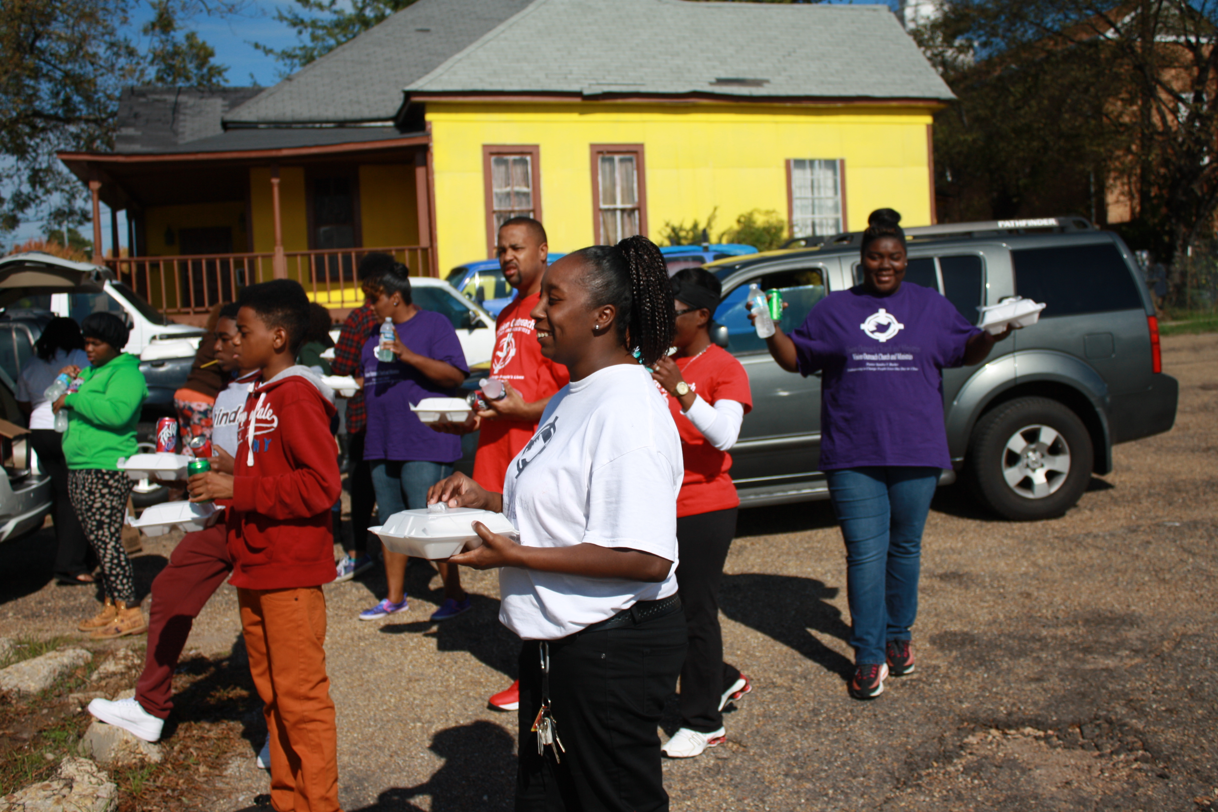Members of Vision Outreach Church and Ministries await individuals to give meals to on Rose Street in Jackson. Photos by Shanderia K. Posey