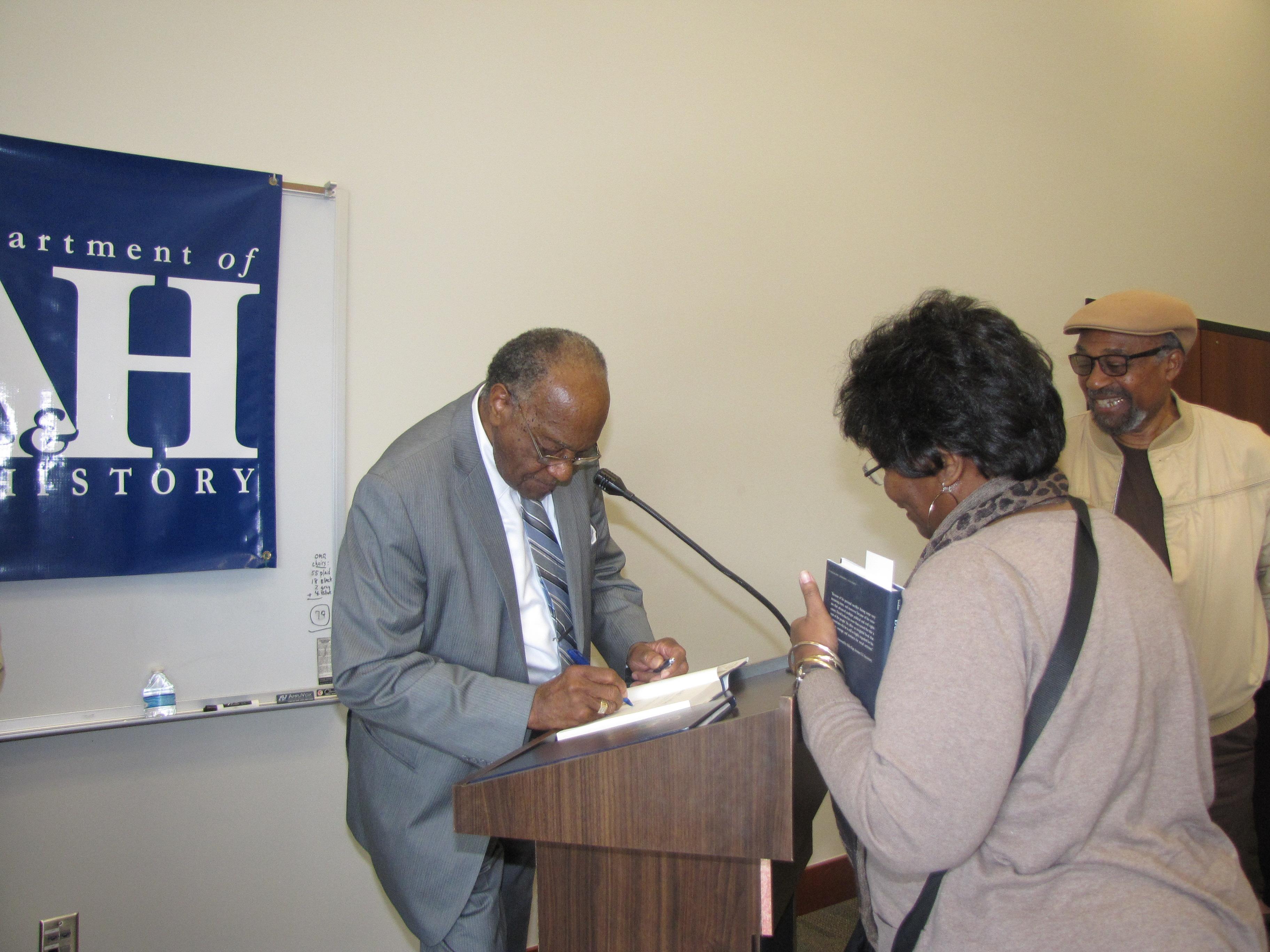 Sen. David Jordan signs book for attender. Photo by Janice K. Neal-Vincent