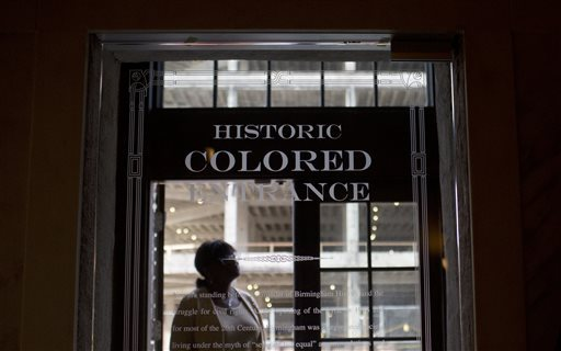 """In this Thursday, Jan. 7, 2016 photo, a woman stands in the doorway of then new Historic Colored Entrance at the Lyric Theatre, in Birmingham, Ala. Preservationists had to decide whether to keep reminders of The Lyric's discarded color line before they unveiled an $11 million restoration of the 102-year-old theater, which had been closed for decades. In this case, they chose to highlight the history, installing a glass door with the etched words """"Historic Colored Entrance"""" in the lobby wall so patrons can peer into the past. (Brynn Anderson/The Associated Press)"""