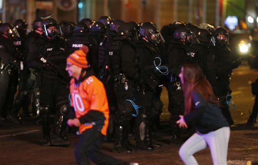 Denver Broncos fans run past a phalanx of Denver Police Department officers in riot gear as fans celebrate the team's victory over the Carolina Panthers in Super Bowl 50 late Sunday, Feb. 7, 2016, in Denver. (David Zalubowski/The Associated Press)
