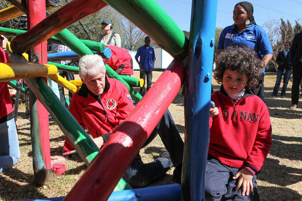 In this Aug. 8, 2015 file photo, former President Bill Clinton helps paint a jungle gym during a visit to a Clinton Foundation project in Johannesburg. As Bill Clinton's presidency ended, he was popular, yet still tainted by scandal, and struggling to find his footing after eight years in the White House. He eventually channeled his energy into the global philanthropy that bears his name and has shaped so much of his post-presidential legacy. (AP Photo Jordi Matis, File)