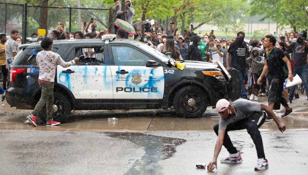 During a protest over the police killing of George Floyd, protesters gather in the back of the precinct where some of the protesters picked up rocks and medal objects to smash the windows of a squad car in the back on May 26, 2020. (Chris Juhn/Zenger)